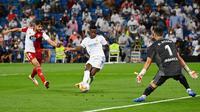 Pemain Real Madrid Brasil Vinicius Junior (tengah) mencetak gol ke gawang Celta Vigo pada pertandingan Liga Spanyol di Stadion Santiago Bernabeu, Madrid, Spanyol, 12 September 2021. Karim Benzema mencetak hattrick saat Real Madrid mengalahkan Celta Vigo 5-2. (GABRIEL BOUYS/AFP)