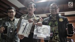 Kasubag Opinev Bag Penum Humas Polri AKBP Zahwani Pandra Arsyad (tengah) menunjukkan barang bukti saat rilis kasus sindikat sextortion atau pemerasan melalui video call sex di Bareskrim Polri, Jakarta, Jumat (15/2). (Liputan6.com/Faizal Fanani)