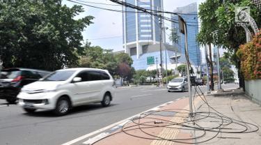 Kendaraan melintas dekat kabel listrik yang menjuntai di Jalan Haji Agus Salim, Jakarta, Minggu (9/9). Instalasi kabel yang menjuntai ke jalan akibat tersangkut truk itu dapat membahayakan warga dan pengendara yang melintas (Merdeka.com/ Iqbal S. Nugroho)