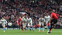 Gelandang Manchester United, Paul Pogba saat mengeksekusi penalti ke gawang West Ham United selama pertandingan lanjutan Liga Inggris di Old Trafford (13/4). Pogba mencetak dua gol lewat titik penalti mengantar MU menang tipis 2-1 atas West Ham. (AFP Photo/Paul Ellis)