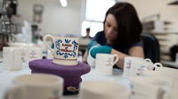 Tampilan mug untuk merayakan pernikahan Pangeran Harry dan Meghan Markle yan telah selesai dibuat di pabrik Emma Bridgewater di Stoke-on-Trent, Inggris (16/4). Pangeran Harry dan Meghan Markle akan menikah pada 19 Mei 2018. (AFP/Oli Scarff)
