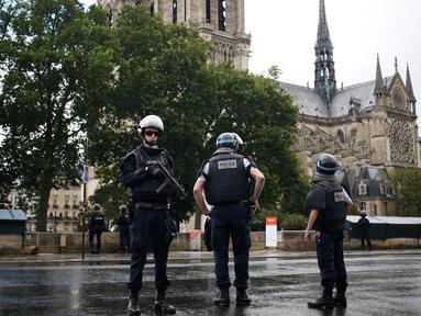 Petugas kepolisian menutup akses menuju Katedral Notre-Dame di Paris setelah aksi penyerangan, Selasa (6/6). Kepolisian Paris menembak seorang pria yang mencoba menyerang perwira polisi di kawasan Katedral Notre Dame. (AP Photo/Matthieu Alexandre)