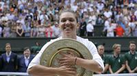 Simona Halep memeluk trofi Wimbledon usai mengalahkan Serena Williams 6-2, 6-2 di final, Sabtu (13/7/2019). (AP Photo/Kirsty Wigglesworth)