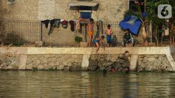 Sejumlah anak mandi di setu Rawabadung, Jakarta, Sabtu (19/10/2019). Cuaca yang panas membuat sejumlah anak untuk mandi di Setu Rawabadung tanpa mengenal resiko bahaya tenggelam. (merdeka.com/Imam Buhori)