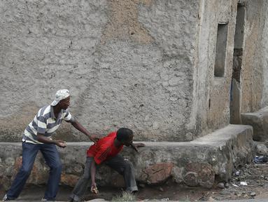 Pengunjuk rasa sembunyi dibalik dinding dengan membawa batu bersiap menyerang petugas di Bujumbura, Burundi, (20/5/2015). Kerusuhan dipicu protes terhadap Presiden Burundi Pierre Nkurunziza untuk upayanya menambah masa jabatan. (REUTERS/Goran Tomasevic)