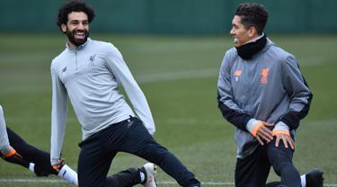 Penyerang Liverpool, Mohamed Salah (kiri) dan Roberto Firmino melakukan pemanasan saat latihan di Melwood Training Ground, Liverpool, Inggris (5/3). Liverpool akan melawan Porto pada leg kedua babak 16 besar Liga Champions. (AFP Photo/Anthony Devlin)
