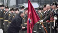 Presiden Ukraina Petro Poroshenko mengambil topi seorang tentara militer saat dia dan Presiden Austria Alexander van der Bellen dalam sebuah upacara penyambutan di Kiev, Ukraina, Rabu, (14/3). (AP Photo / Efrem Lukatsky)
