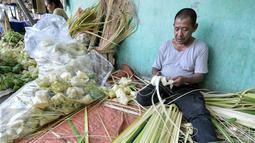 Pedagang membuat kulit ketupat untuk dijual di Pasar Minggu, Jakarta Selatan, Senin (4/7). H-2 Hari Raya Idul Fitri, pedagang kulit ketupat mulai kebanjiran pembeli. (Liputan6.com/Yoppy Renato)