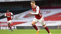 Pemain Arsenal, Martin Odegaard, melakukan selebrasi usai mencetak gol ke gawang Tottenham Hotspur pada laga Liga Inggris di Stadion Emirates, Minggu (14/3/2021). Arsenal menang dengan skor 2-1. (Dan Mullan/Pool via AP)