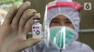 Bidan lengkap dengan baju Alat Pelindung Diri (APD) menunjukan vaksin DPT untuk anak di Posko Imunisasi, Kelurahan Bakti Jaya, Tangerang Selatan, Senin (11/5/2020). Pelayanan imunisasi tetap berjalan sesuai jadwal meski pandemi Covid-19. (Liputan6.com/Fery Pradolo)