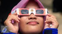 Seorang mahasiswi mencoba kacamata yang akan di gunakan untuk mengamati gerhana matahari di taman Pintar Yogyakarta, (2/3). Kawasan Tugu menjadi salah satu tempat pengamatan gerhana matahari pada 9 Maret 2016. (Liputan6.com/Boy Harjanto)