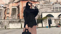 Mantan finalis Gadis Sampul 2007 ini tampak modis dengan hijab dan atasan berwarna hitam dipadu dengan rok panjang berwarna krem saat berpose di Hagia Sophia, Turki. (Liputan6.com/IG/@citraciki)