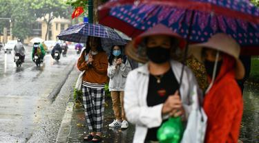 Para penumpang menunggu di halte bus selama hujan lebat di Hanoi (14/10/2020). Badai tropis Nangka menghantam Vietnam tengah-utara yang mengakibatkan bencana alam, terutama hujan lebat dan banjir, telah menyebabkan 28 orang tewas dan 12 lainnya hilang. (AFP Photo/Manan Vatsyayana)