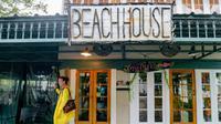 Aimee Cutter, pemilik restoran Beach House, berjalan menembus banjir kiriman dari Danau Pontchartrain di Lakeshore Drive, Mandeville, La., akibat dampak Badai Tropis Barry, Sabtu, 13 Juli 2019. (Matthew Hinton/AP)