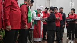 Ketua Umum PDIP Megawati Soekarnoputri menyerahkan KTA PDIP kepada tokoh agama di Jakarta, Selasa (2/4). Sejumlah tokoh agama, purnawirawan TNI-Polri, dan akademisi menyatakan bergabung dengan PDIP. (Liputan6.com/Faizal Fanani)