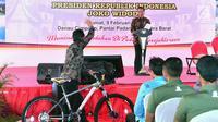 Seorang warga melambaikan tangan ke Presiden Jokowi usai mendapat hadiah sepeda dalam HPN 2018 di Padang, Sumatera Barat, Jumat (9/2). (Liputan6.com/Pool/Biro Setpres)