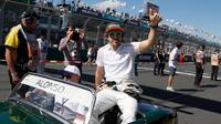 Pembalap F1 tim McLaren, Fernando Alonso duduk di atas mobil saat mengikuti parade jelang balapan pertama musim ini di GP F1 Australia di Melbourne, Australia, (25/3). Alonso akan memulai balapan dari posisi ke-11. (AP Photo/Asanka Brendon Ratnayake)
