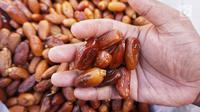 Pedagang kurma menunjukkan barang dagangannya di Pasar Tanah Abang, Jakarta, Kamis (2/5). Menjelang bulan Ramadan, permintaan buah kurma meningkat dua kali lipat dibanding hari biasa. (Liputan6.com/JohanTallo)