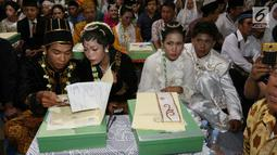 Sejumlah pasangan mengikuti nikah massal di malam pergantian tahun di Jalan MH Thamrin, Jakarta, Minggu (31/12). Sebanyak 430 pasangan melakukan nikah massal melalui seleksi yang cukup ketat oleh pemprov DKI Jakarta. (Liputan6.com/Angga Yuniar)