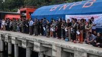Keluarga dan warga berdoa untuk penumpang yang hilang dari kecelakaan KM Sinar Bangun di Danau Toba di Pelabuhan Tigaras, Sumatra Utara, Indonesia (21/6). KM Sinar Bangun tenggelam pada Senin (18/6) sore. (AFP Photo/Ivan Damanik)