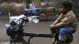 Seorang anak duduk di atas becak seekor sapi ditutupi dengan karung goni di pinggir jalan di New Delhi, India, Selasa (5/1/2021). Pemilik sengaja memakaikan penutup pada tubuh sapi untuk melindungi sapi dari cuaca dingin. (Photo by Sajjad HUSSAIN / AFP)