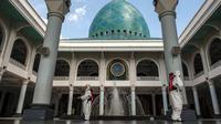 Pekerja dari otoritas penanggulangan bencana setempat menyemprotkan desinfektan di sebuah masjid di Surabaya, Jawa Timur, Selasa (17/3/2020). Kegiatan tersebut dilakukan untuk mencegah penyebaran Virus Corona COVID-19. (Photo by Juni Kriswanto / AFP)