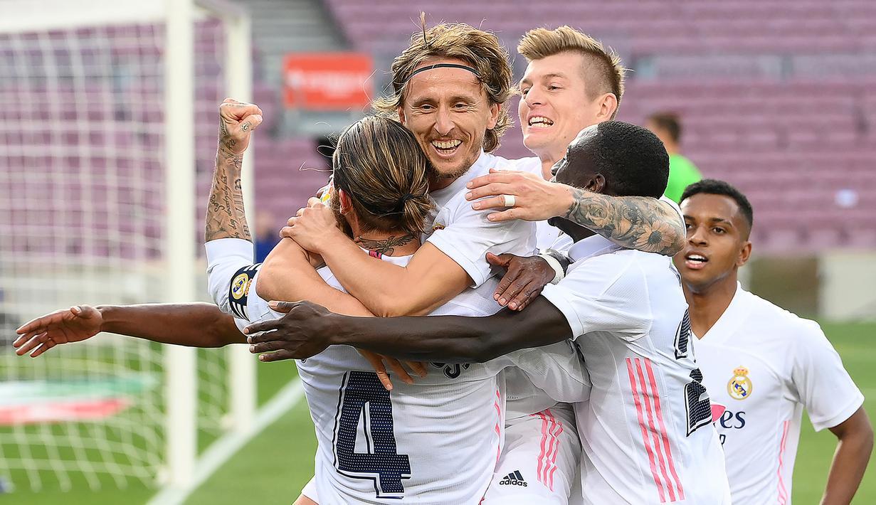 Pemain Real Madrid merayakan gol yang dicetak Luka Modric ke gawang Barcelona pada laga Liga Spanyol di Camp Nou Stadion, Sabtu (24/10/2020) malam WIB. Real Madrid menang 3-1 atas Barcelona. (AFP/Lluis Gene)