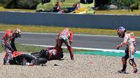Pembalap Repsol Honda, Dani Pedrosa berjalan menuju pembalap Ducati, Andrea Dovizioso dan Jorge Lorenzo setelah mengalami tabrakan pada MotoGP Spanyol 2018 di Sirkuit Jerez, Minggu (6/5). Ketiganya gagal merampungkan balapan balapan.  (AFP/JAVIER SORIANO)