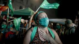 Aktivis hak-hak aborsi menangis setelah anggota parlemen menyetujui undang-undang yang melegalkan aborsi di luar Kongres, Buenos Aires, Argentina, Rabu (30/12/2020). Argentina memastikan sebagai negara Amerika Latin pertama yang melegalkan aborsi. (AP Photo/Natacha Pisarenko)
