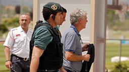 Polisi Spanyol mengawal Angel Maria Villar saat dibawa ke markas besar Federasi di Las Rozas, Spanyol (18/7). Villar terlibat kasus pemalsuan dokumen serta penyalahgunaan wewenang yang melibatkan kepentingan timnas Spanyol. (AP Photo / Francisco Seco)