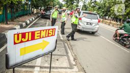Polisi mengatur lalu lintas saat uji emisi gas buang kendaraan bermotor di Jakarta, Rabu (6/1/2021). Pengecekan yang diselenggarakan Dinas Perhubungan dan Kepolisian tersebut bertujuan untuk mengurangi polusi udara dari emisi gas buang kotor. (Liputan6.com/Faizal Fanani)
