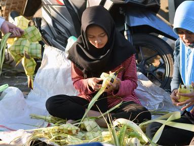 Pedagang merangkai janur menjadi kulit ketupat di Pasar Peterongan Semarang, Jawa Tengah, Kamis (14/6). Penjualan ketupat dan janur mulai marak menjelang lebaran dengan harga Rp 12.000 per sepuluh ketupat. (Liputan6.com/Gholib)