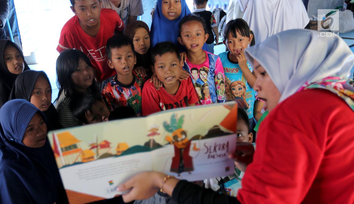 Anak-anak korban gempa tsunami Palu mendengarkan cerita bergambar di halaman kantor Dinas Sosial Palu, Sulawesi Tengah, Sabtu (6/10). Trauma healing diberikan untuk mencegahanakmemiliki kepribadian buruk. (Liputan6.com/Fery Pradolo)