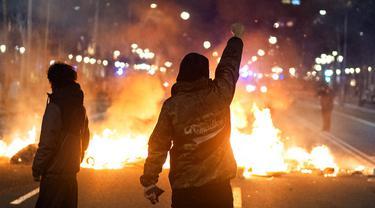 Demonstran bentrok dengan polisi saat memprotes penangkapan rapper Pablo Hasel di Barcelona, Spanyol, Selasa (16/2/2021). Aksi protes meletus di Spanyol setelah polisi menangkap Pablo Hasel yang menolak hukuman penjara karena menghina kerajaan dan memuji terorisme. (AP Photo/Emilio Morenatti)