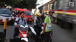 Kereta api melintas di kawasan Lenteng Agung, Jakarta, Kamis (14/3). Pembangunan jalan layang (fly over) berbentuk tapal kuda di perlintasan kereta tersebut diprediksi akan mengurangi tingkat kemacetan antara 40-50 persen. (Liputan6.com/Immanuel Antonius)