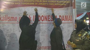 Sejumlah warga menandatangani spanduk saat tablig akbar di Simpang Lima, Kota Semarang, Minggu (13/5). Spanduk tersebut bentuk dukacita untuk korban teror di Mako Brimob, Jakarta beberapa waktu lalu dan teror bom gereja di Surabaya. (Liputan6.com/Gholib)