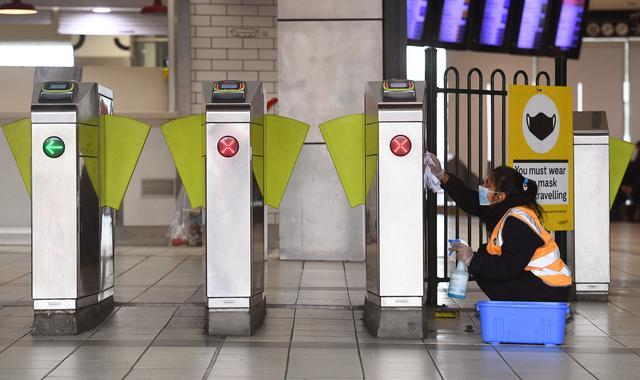 Petugas membersihkan gate Stasiun Flinders Street selama jam sibuk yang biasanya ramai saat pemberlakukan lockdown di Melbourne, Jumat (28/5/2021). Melbourne kembali menerapkan lockdown untuk keempat kalinya setelah wabah COVID-19 menyebar cepat di wilayah tersebut. (William WEST/AFP)