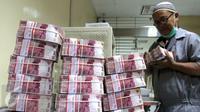Petugas sedang merapikan uang di ruang penyimpanan uang BNI, Jakarta, Senin (2/11/2015). Lembaga Penjamin Simpanan (LPS) mencatat jumlah rekening simpanan dengan nilai di atas Rp2 M pada bulan September mengalami peningkatan . (Liputan6.com/Angga Yuniar)