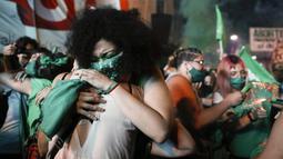 Aktivis hak-hak aborsi berpelukan sambil menangis setelah anggota parlemen menyetujui undang-undang yang melegalkan aborsi di luar Kongres, Buenos Aires, Argentina, Rabu (30/12/2020). Ini merupakan puncak bagi para aktivis perempuan setelah bertahun-tahun lamanya. (AP Photo/Natacha Pisarenko)