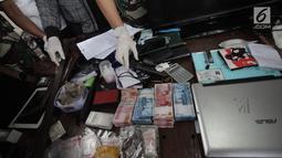 Sejumlah uang dan sebuah senjata api yang berhasil diamankan petugas saat penggerebekan di Kampung Ambon, Cengkareng, Jakarta, Rabu (24/1). Petugas juga berhasil mengamankan senjata api berikut amunisi, dan senjata tajam. (Liputan6.com/Arya Manggala)