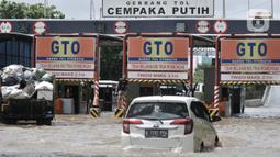 Mobil nekat menerobos banjir menuju Gerbang Tol Cempaka Putih, Jakarta, Minggu (23/2/2020). Banjir yang melanda kawasan tersebut menyebabkan Gerbang Tol Cempaka Putih tidak dioperasikan akibat terendam hingga ketinggian mencapai sepinggang orang dewasa. (merdeka.com/Iqbal S. Nugroho)