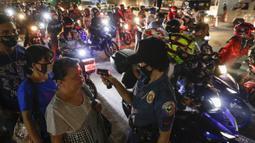 Polisi memeriksa suhu tubuh warga di pos pemeriksaan virus corona COVID-19 di Manila, Filipina, Senin (16/3/2020). Polisi beserta petugas lalu lintas dan petugas desa melakukan pengecekan suhu tubuh warga untuk mencegah penyebaran virus corona COVID-19. (AP Photo/Aaron Favila)
