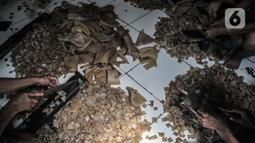 Pekerja menyelesaikan pembuatan kerupuk kulit di industri rumahan kawasan Bogor, Minggu (26/9/2021). Sebelum Covid-19 melanda biasanya pelaku usaha kerupuk kulit mampu memproduksi 30 lembar kulit sapi dalam sehari, namun kini hanya 12-15 lembar kulit per hari. (merdeka.com/Iqbal S Nugroho)
