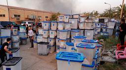 Sejumlah petugas menyelamatkan kotak suara saat kebakaran gudang surat suara terbesar Irak di Baghdad, Minggu (10/6). Penyebab kebakaran di gudang penyimpanan itu juga masih belum jelas. (AP/Karim Kadim)