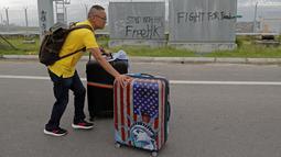 Seorang penumpang membawa koper berjalan kaki ke bandara ketika pemrotes pro-demokrasi memblokir jalan di luar bandara di Hong Kong (1/9/2019). Akibat pemblokiran jalan dan layanan kereta api para calon penumpang pesawat terpaksa berjalan kaki menuju bandara. (AP Photo/Kin Cheung)