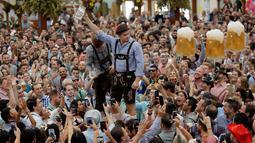 Seorang pria menunjukkan gelasnya yang sudah kosong usai meminum bir saat pembukaan festival bir terbesar di dunia Oktoberfest ke-185 di Munich, Jerman, Sabtu (22/9). (AP Photo/Matthias Schrader)