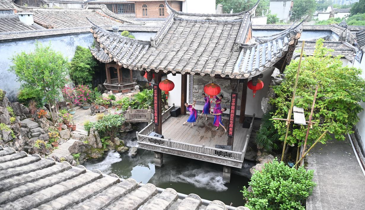 Para staf tampil dalam siaran langsung daring (livestreaming) melalui ponsel di sebuah kawasan sejarah dan budaya di Fuzhou, Provinsi Fujian, China tenggara, (19/5/2020). Tanggal 19 Mei diperingati sebagai Hari Pariwisata China. (Xinhua/Lin Shanchuan)