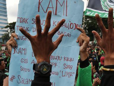 Pengemudi ojek online (ojol) membawa poster saat berdemonstrasi di depan Gedung DPR/MPR, Senayan, Jakarta, Jumat (28/2/2020). Mereka menyampaikan tuntutan terkait UU No 22/2009 itu direvisi dan menjadikan kendaraan roda dua sebagai transportasi khusus terbatas. (Liputan6.com/Johan Tallo)