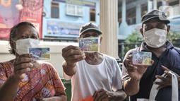 Warga lansia menunjukkan kartu ATM Beras saat menerima bantuan di Kantor RW 02, Kelurahan Cilincing, Jakarta Utara, Rabu (17/3/2021).  Pembuatan ATM Beras secara mandiri sebagai program ketahanan pangan di masa pandemi Covid-19. (merdeka.com/Iqbal S. Nugroho)
