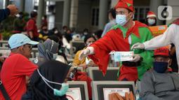 Petugas KAI yang mengenakan kostum Natal membagikan masker kepada calon penumpang di Stasiun Senen, Jakarta, Jumat (25/12/2020). Pembagian ini dilakukan untuk mengganti masker yang sudah dipakai calon penumpang selama perjalanan. (merdeka.com/Imam Buhori)